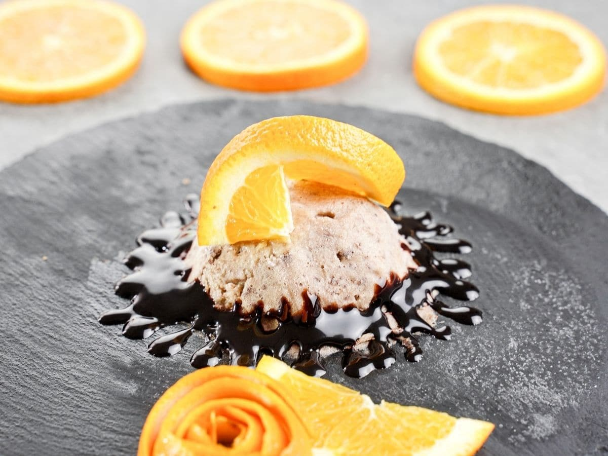 Ice cream on slate plate with sliced oranges in background