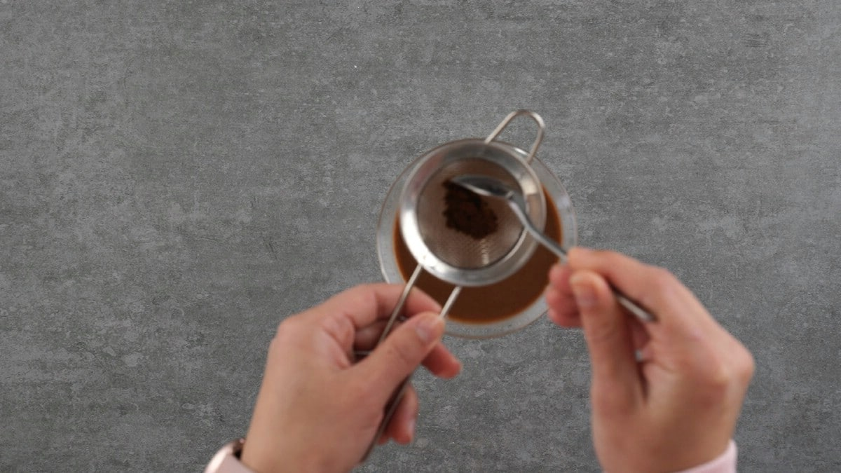 Hand sprinkling espresso powder over top of glass of panna cotta