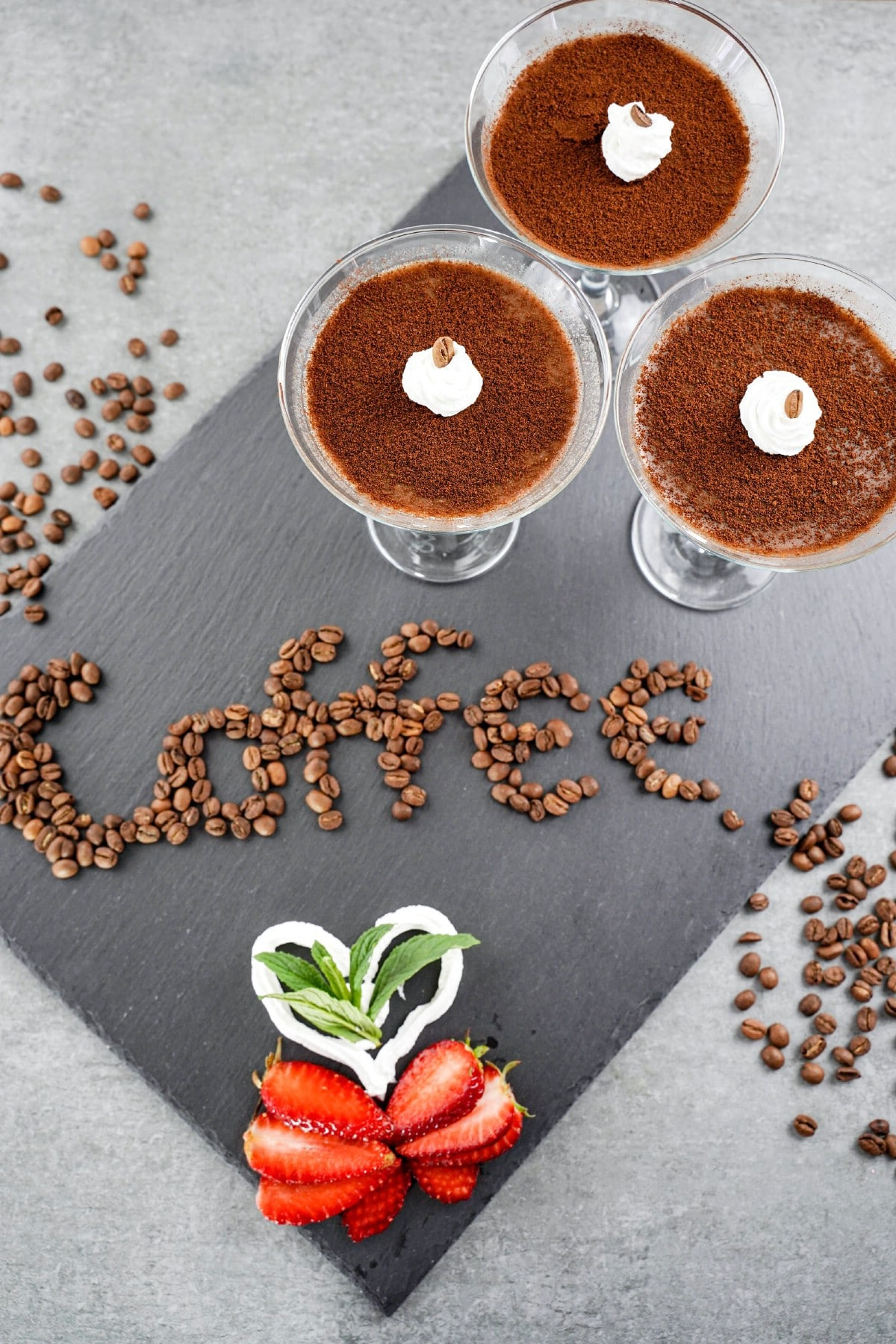 The word coffee spelled out in coffee beans on gray slate with dessert cups in corner