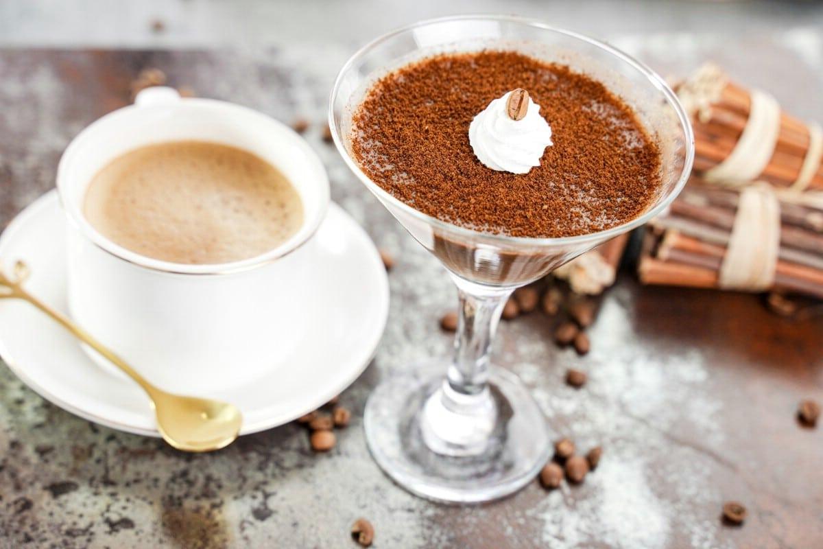 Glass of chocolate panna cotta on gray table next to white coffee mug