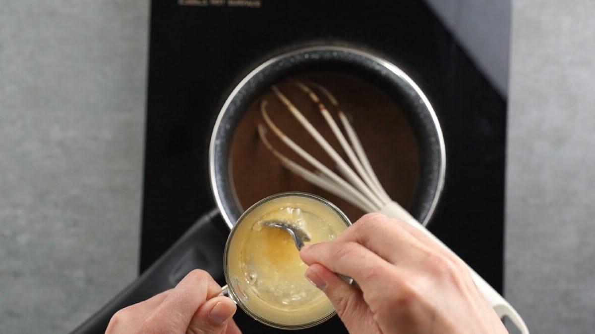 Stirring agar agar in glass jar over top of light teal pan