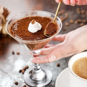 Gold spoon in martini glass of chocolate panna cotta