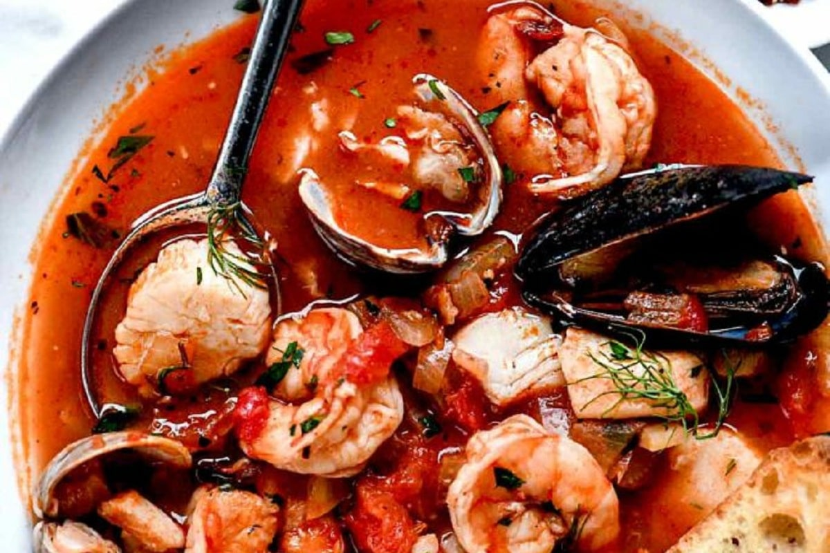 A bowl of seafood (shrimps, cod, mussels) in a chili soup