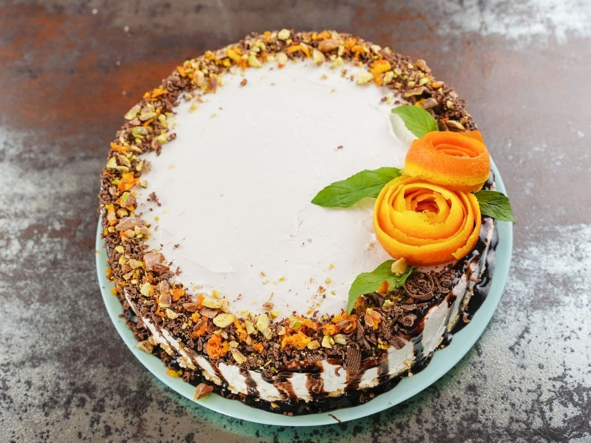 Whole cake topped with orange rose on brown table