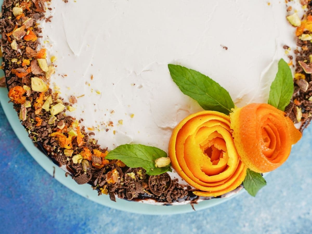 Cake topped with chocolate crumbs and orange rose sitting on blue table