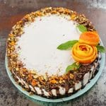 Cheesecake topped with chocolate syrup and orange roses on teal plate