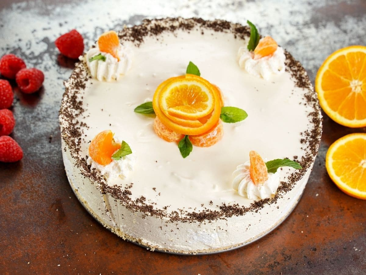 Orange vanilla cheesecake whole on brown table by berries