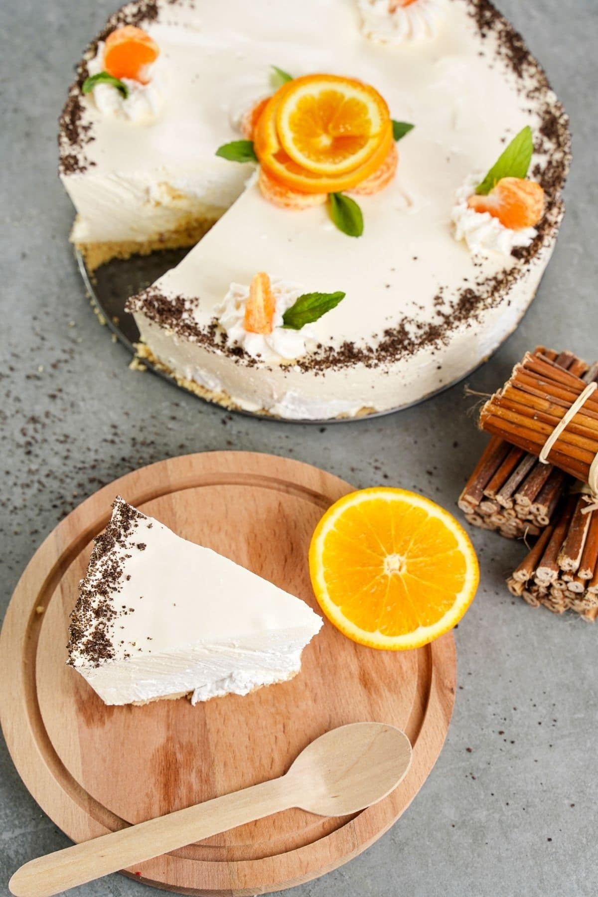 Slice of cheesecake on wooden board next to sliced orange and cinnamon sticks