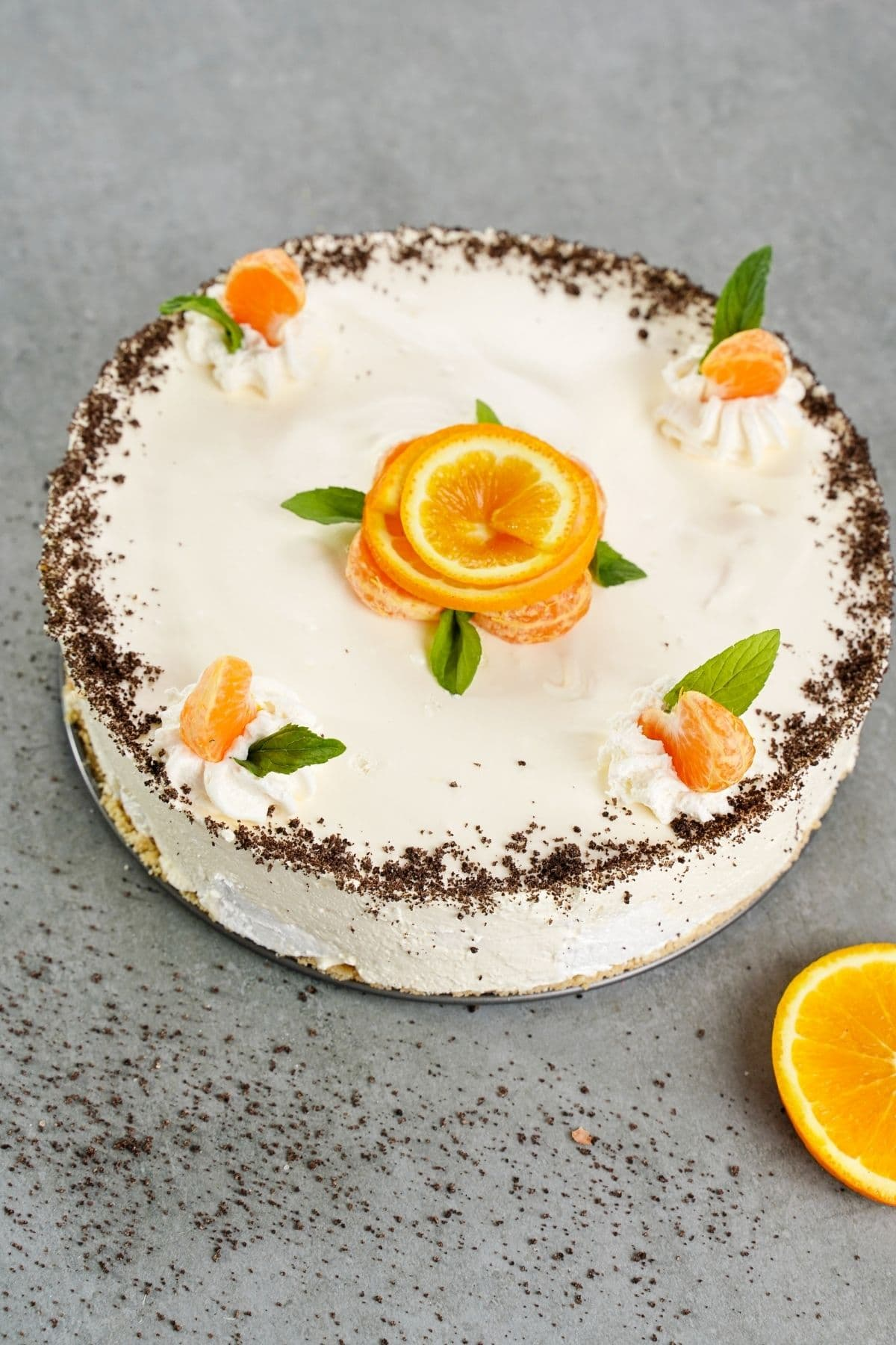 Whole cheesecake on gray table next to orange slices
