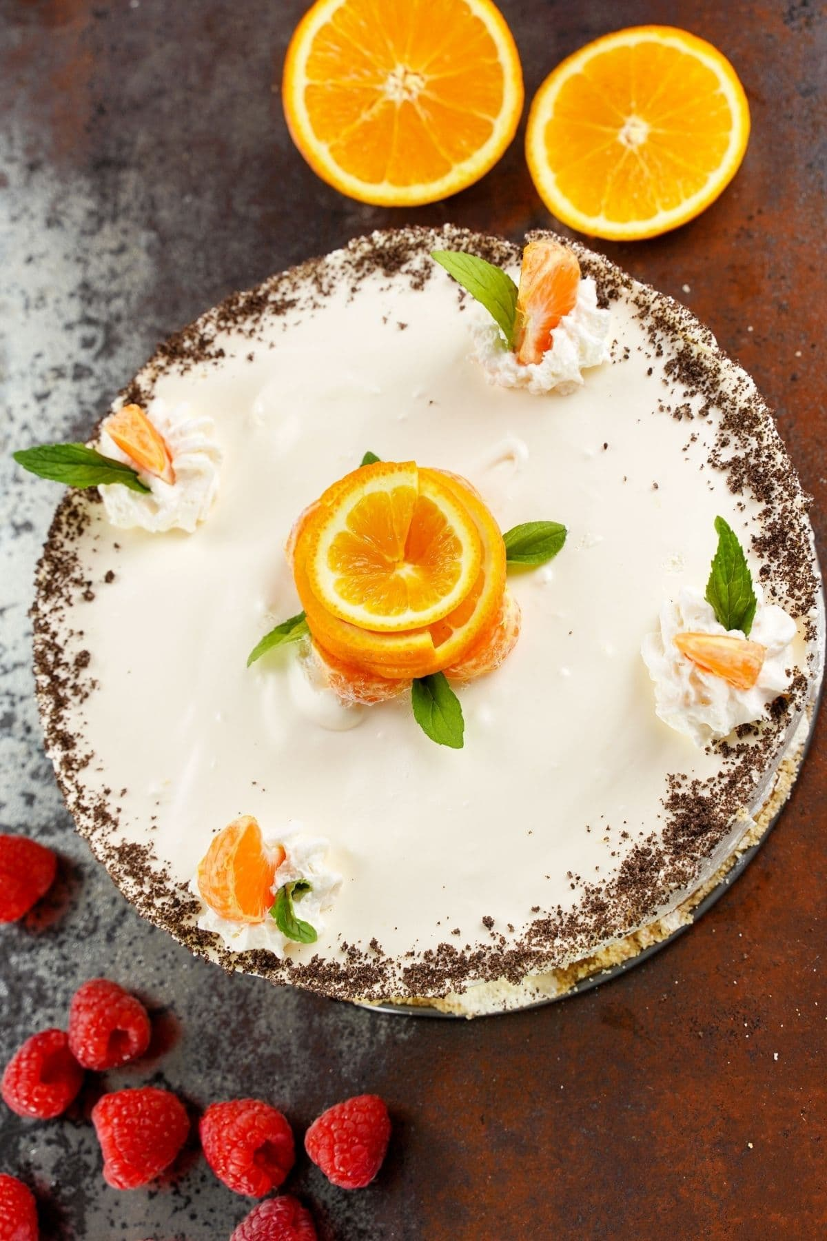 Whole cake topped with orange roses sitting on brown table by raspberries and half an orange