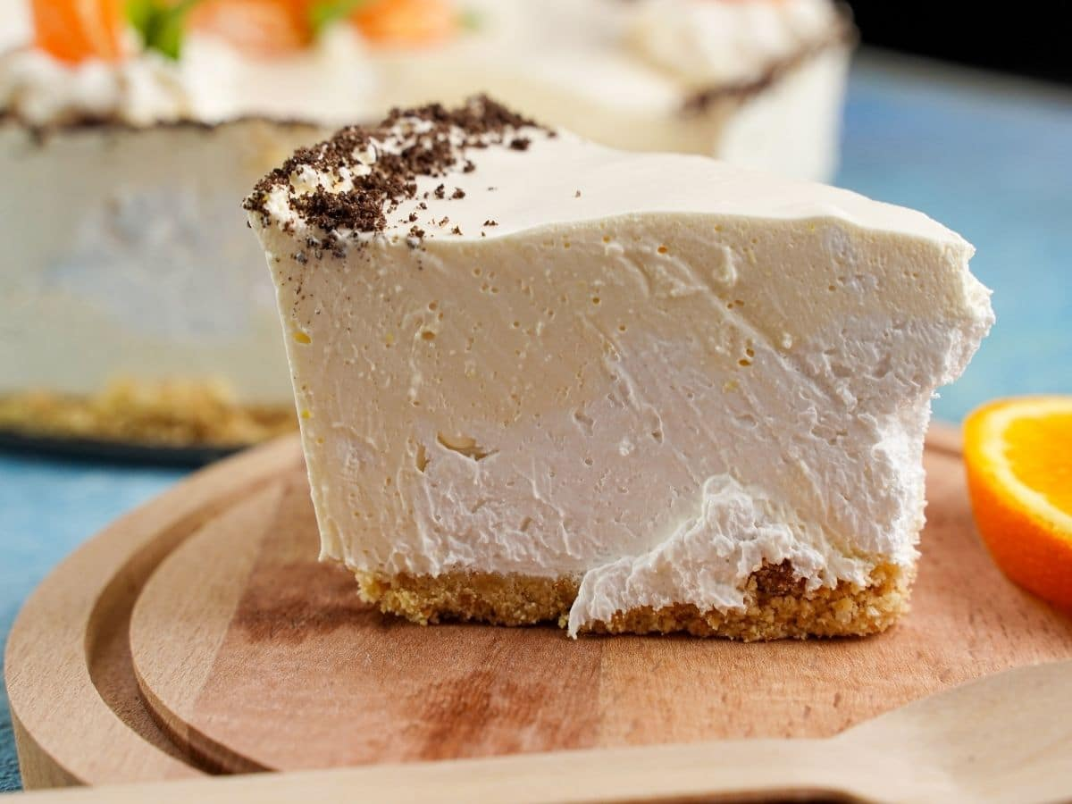Image of the side of a slice of cheesecake showing white and orange layers