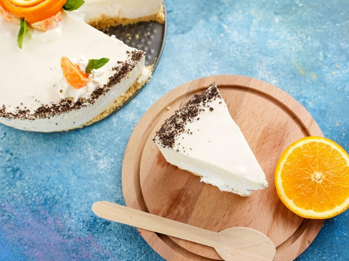 Slice of cake on wooden circle with orange slice on wood that is on blue table