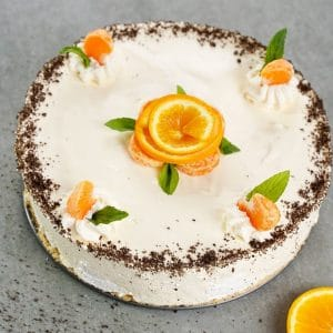 Cheesecake on gray table with orange rind flowers