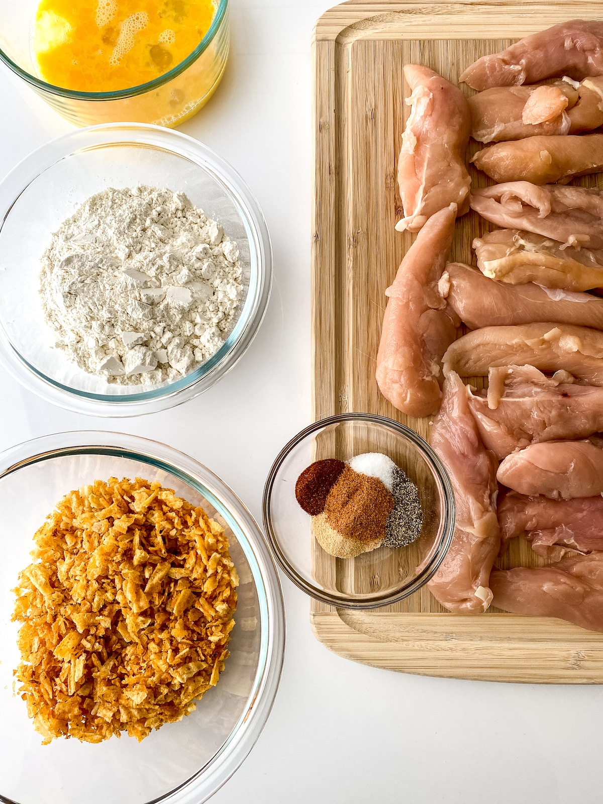Ingredients for chicken tenders on cutting board and in white bowls on table