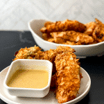 White bowl of chicken tenders on black surface with white saucer of tenders including small bowl of honey mustard