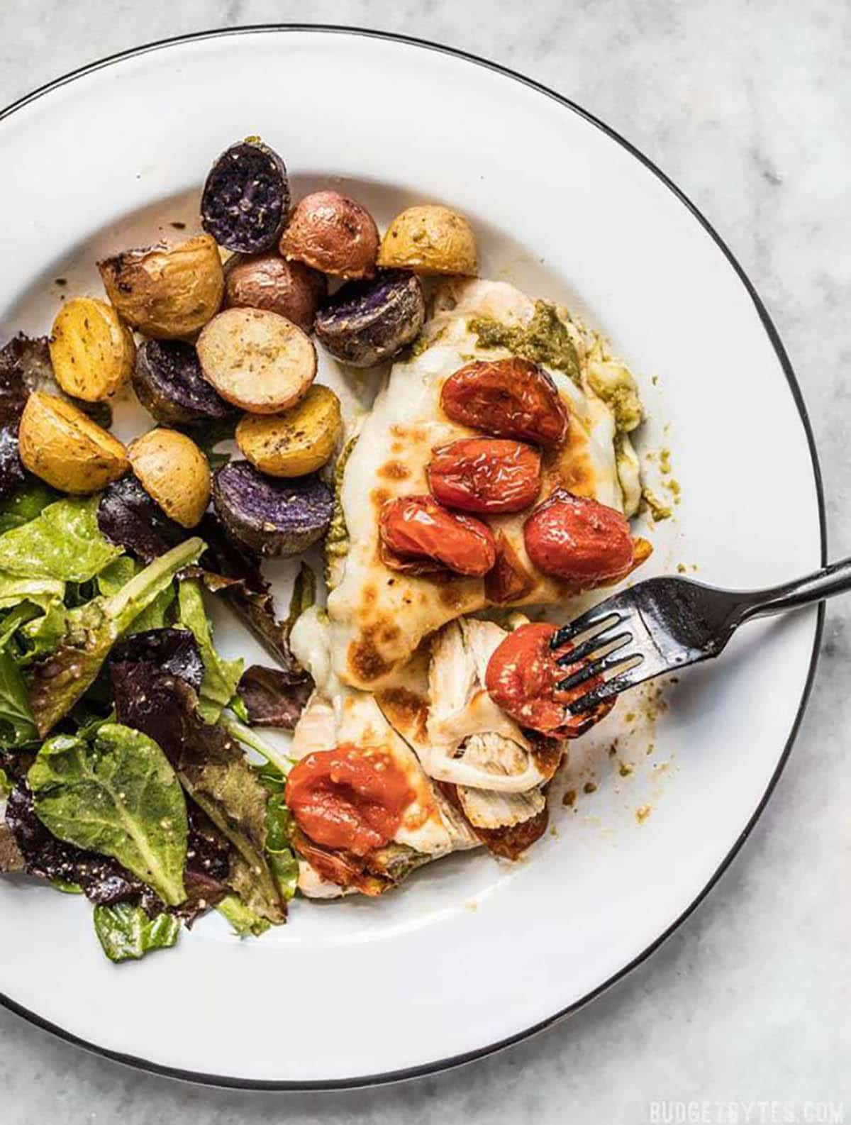Easy Sheet Pan Pesto Chicken Dinner with marble potatoes, salad and topped with cherry tomatoes
