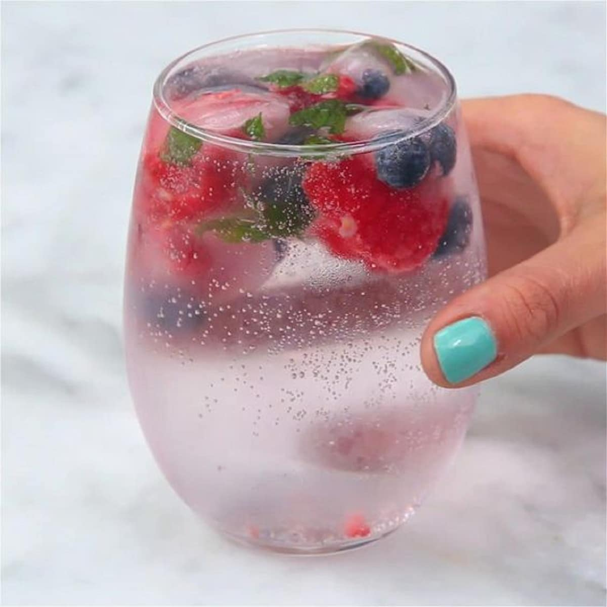 Hand with blue nail polish holding small glass filled with sparkling water and berries