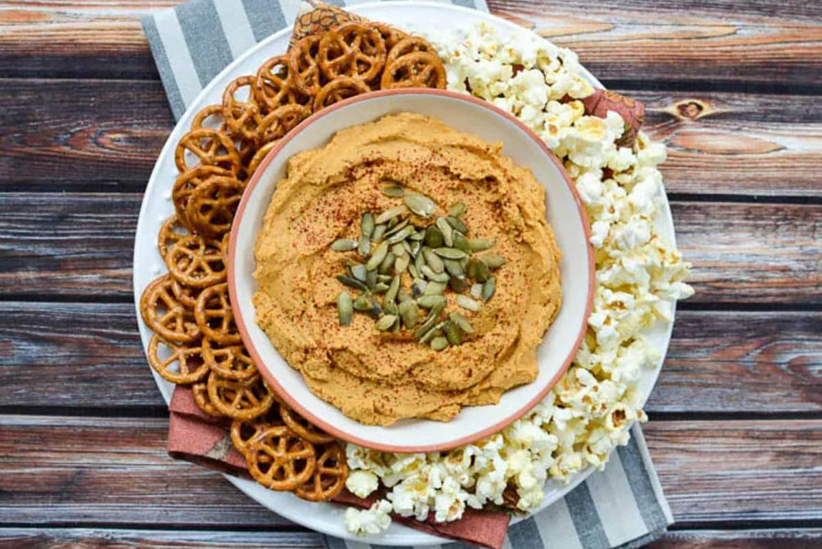 Five-Minute Smoky Pumpkin Hummus topped with smoked chipotle powder and pumpkin seeds. Served with pretzels and popcorn.