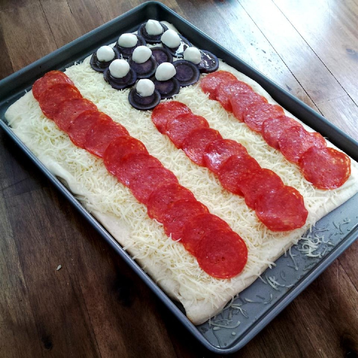 Baking sheet with pizza with decorations in shape of american flag