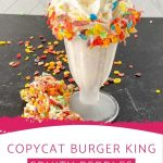 Glass of milkshake topped with colorful cereal on black table with overlay at bottom of image saying copycat burger king fruity pebbles milkshake