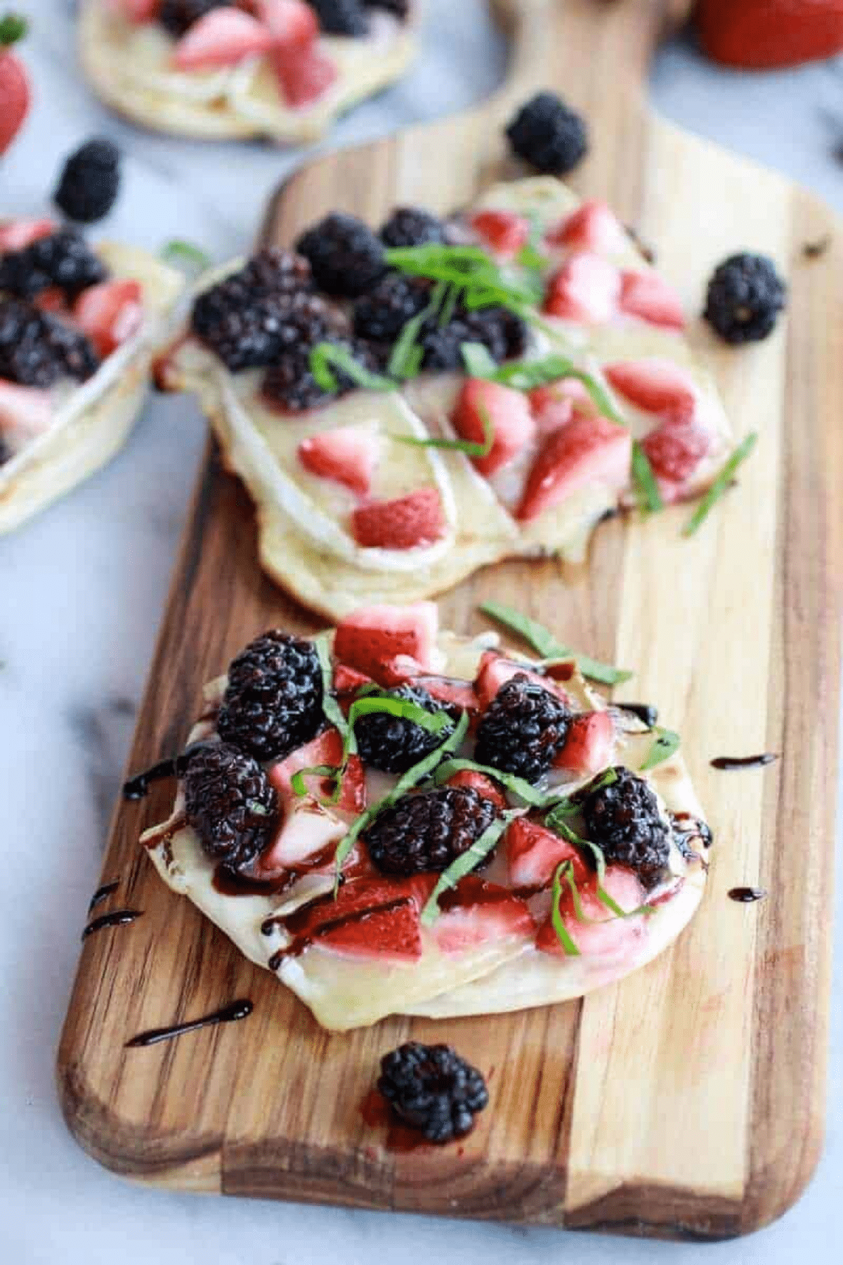 Pizza with berries on top on cutting board