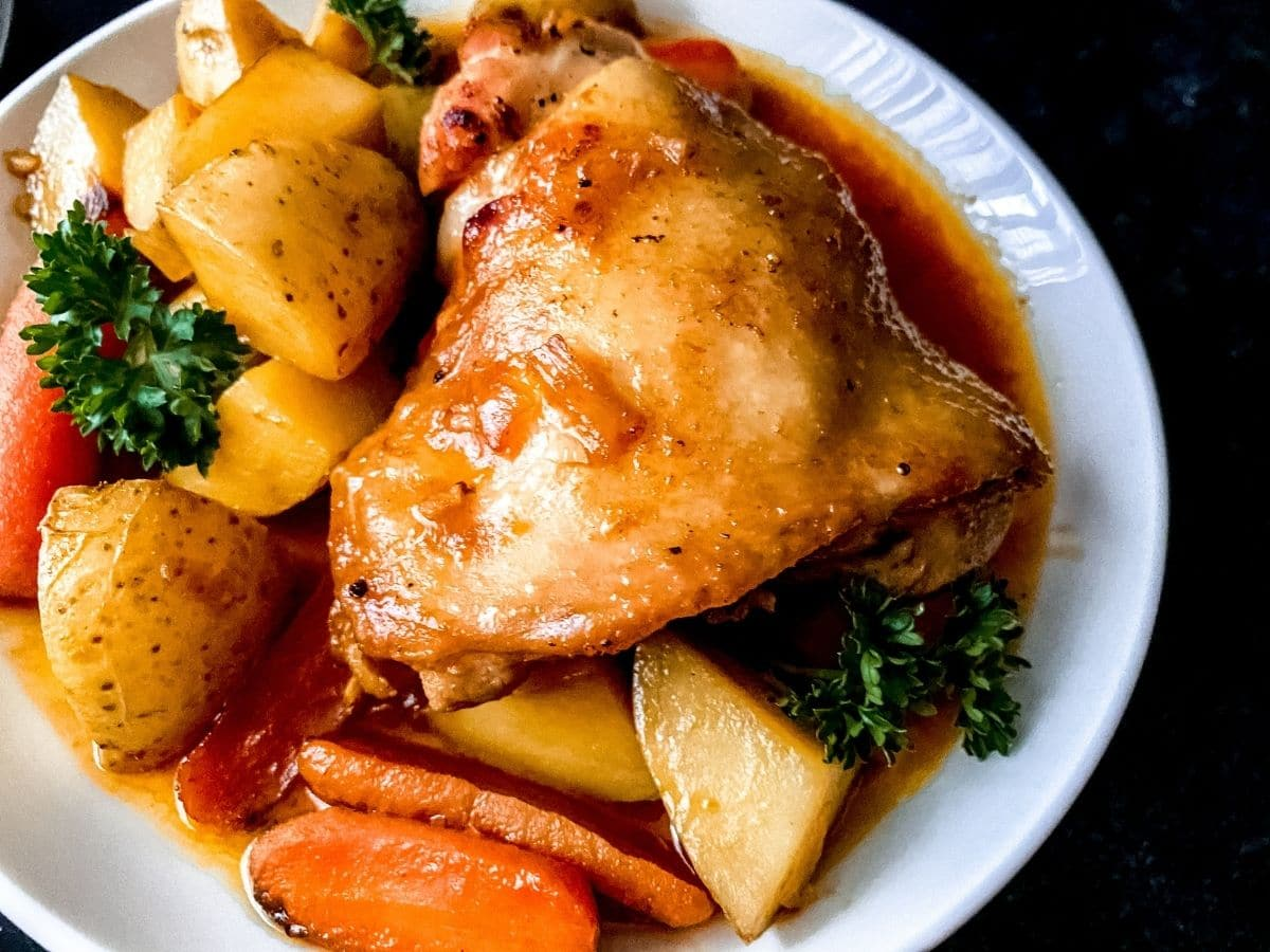 Chicken thigh on plate with orange sauce and potatoes sitting on black table