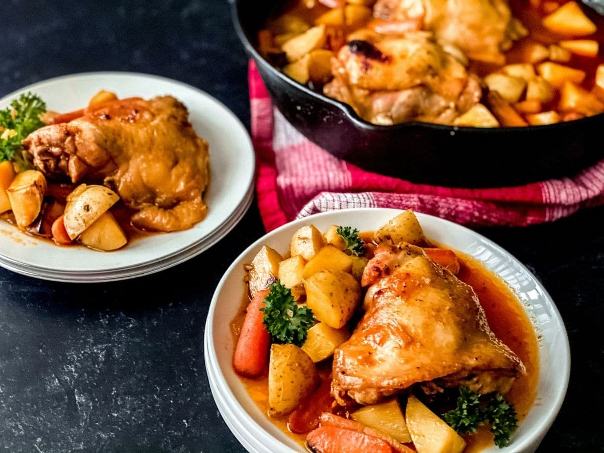 Cast iron skillet with chicken in the background with white plates of garlic chicken and potatoes in foreground