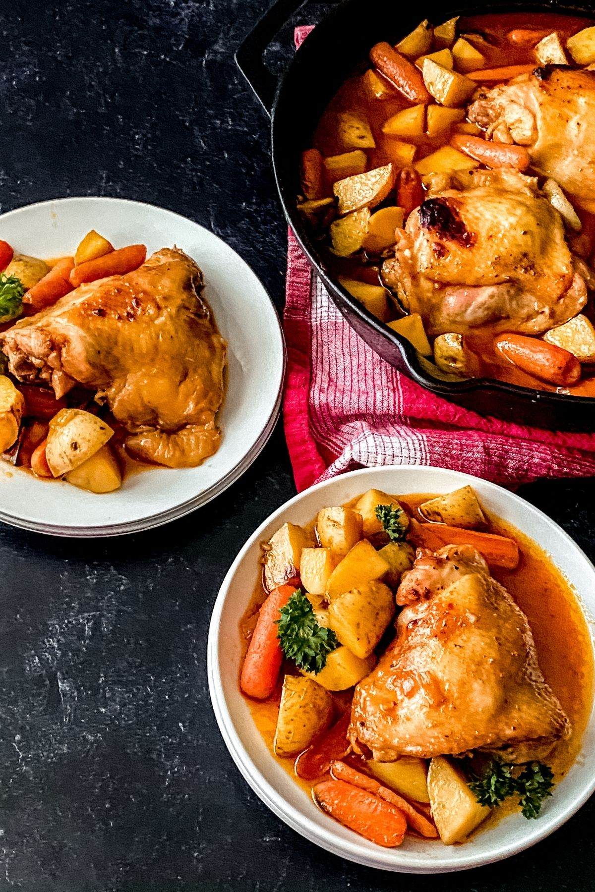 Cast iron skillet on red napkin filled with chicken and vegetables net to white plates of food