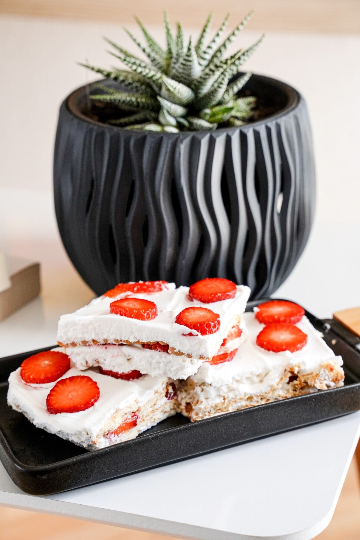 Black platter with slices of strawberry icebox pie sitting in front of black planter