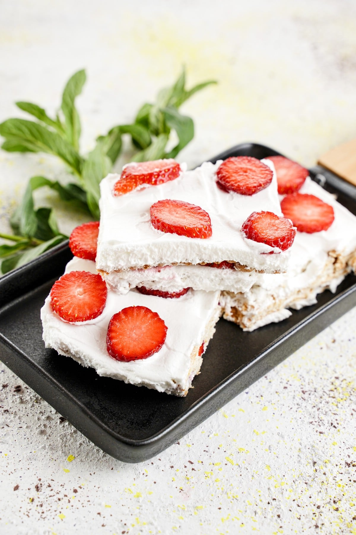 Slices of icebox cake stacked on black platter with mint sprigs in background
