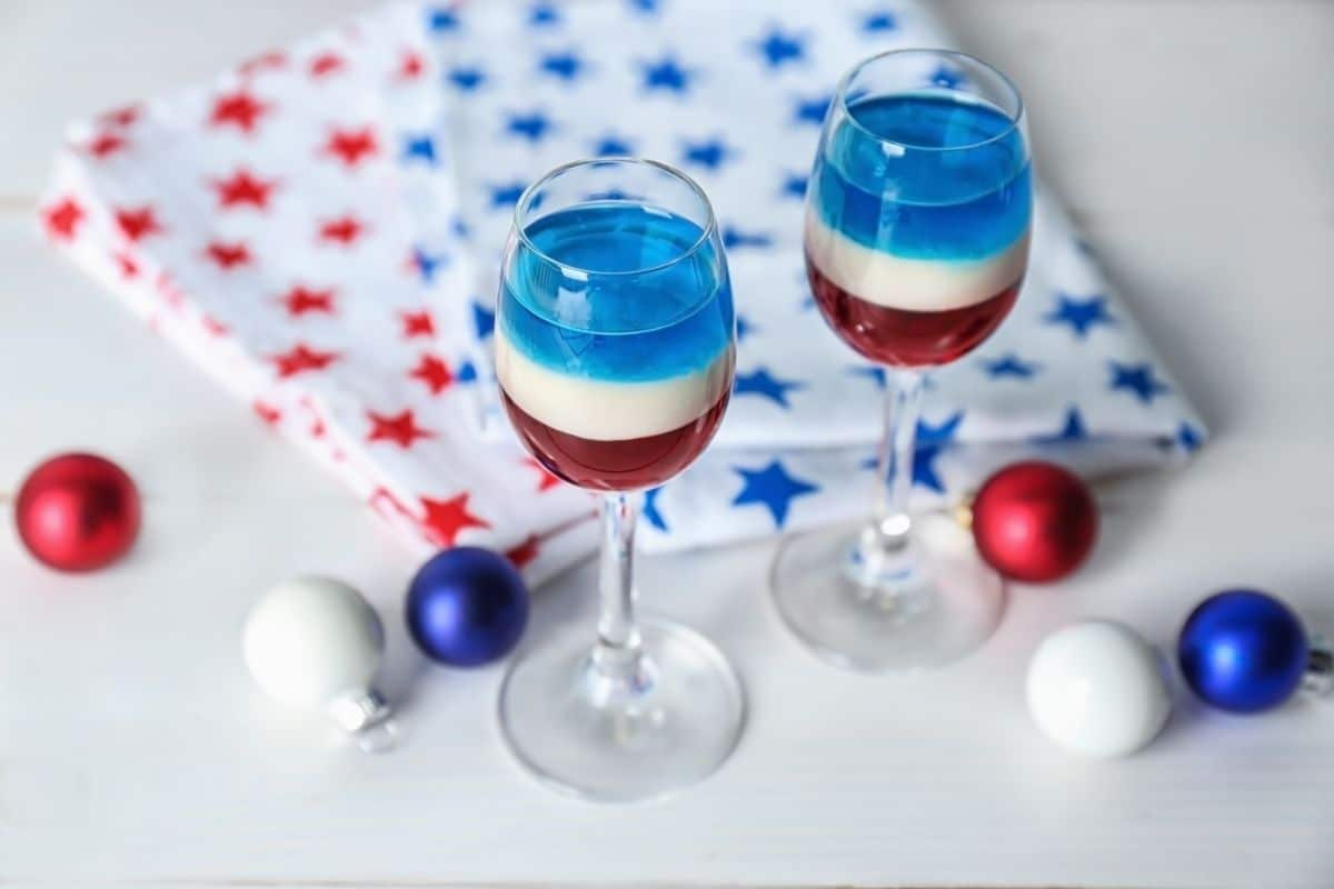 Two wine glasses of layered red white and blue gelatin on white counter by red white and blue balls