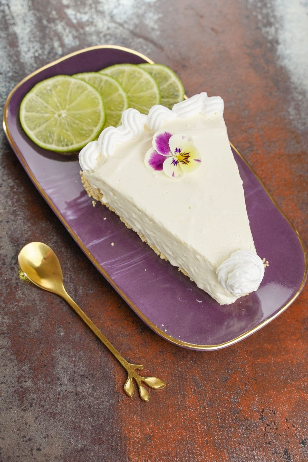 Lemon icebox pie slice on purple plate next to gold spoon