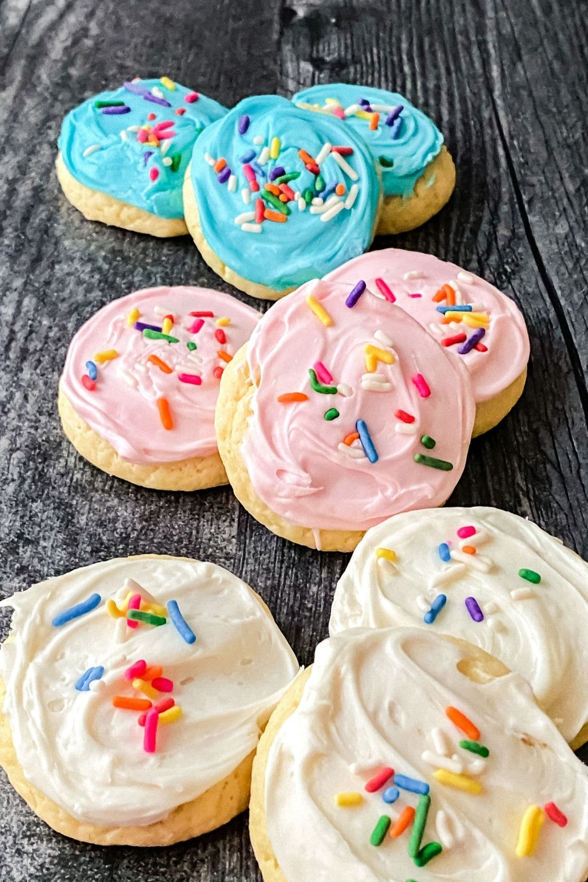 Blue pink and white frosting on cookies laying on gray black table