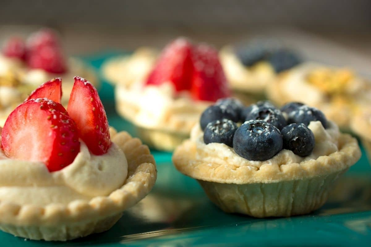 Mini pies on green plate topped with blueberries and strawberries