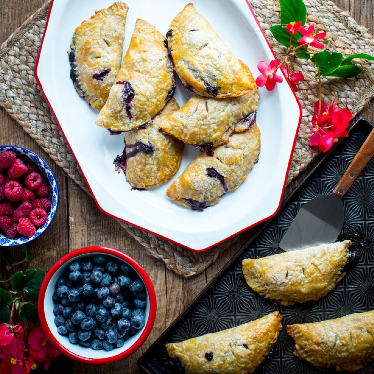 Fried pies stacked on white platter by bowls of raspberries and blueberries