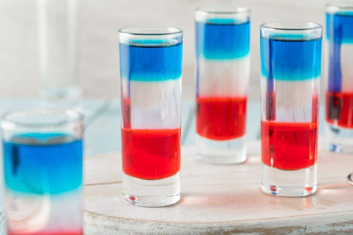 Tall shot glasses on light wood table filled with red white and blue liquid