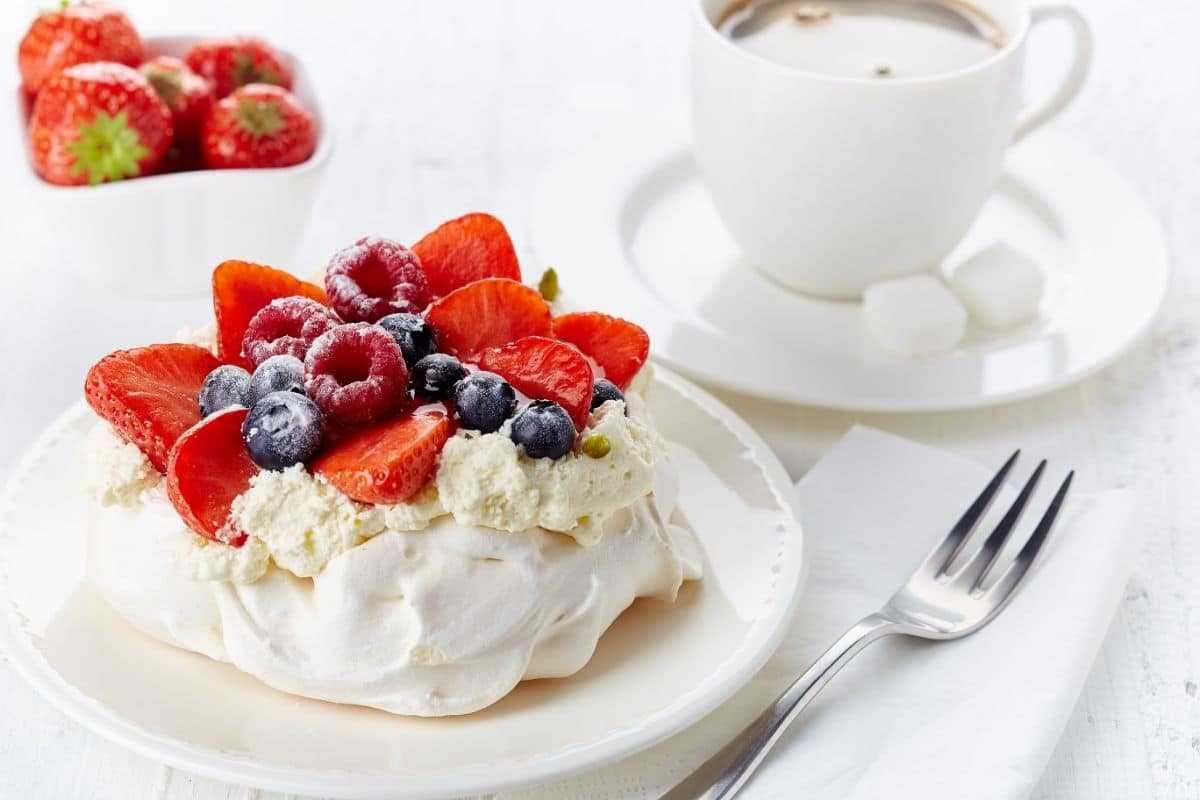 Whipped cream topped with berries on white plate next to cup of coffee