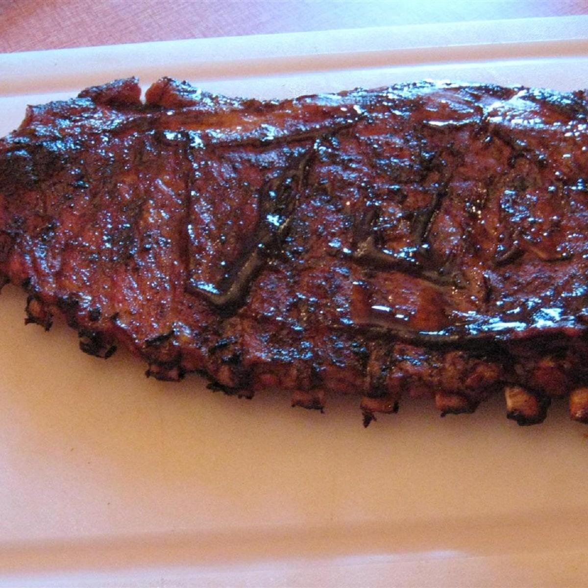 Slab of bbq ribs on white platter
