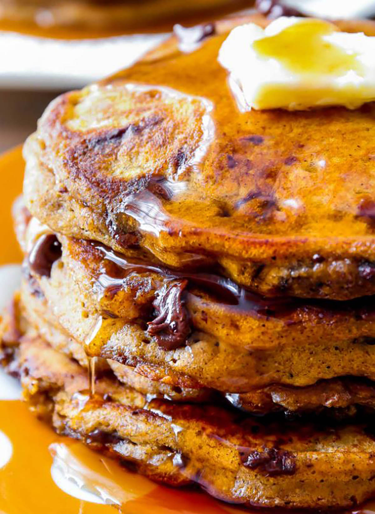 Pumpkin Chocolate Chip Pancakes with pumpkin spice and cinnamon topped with butter and syrup