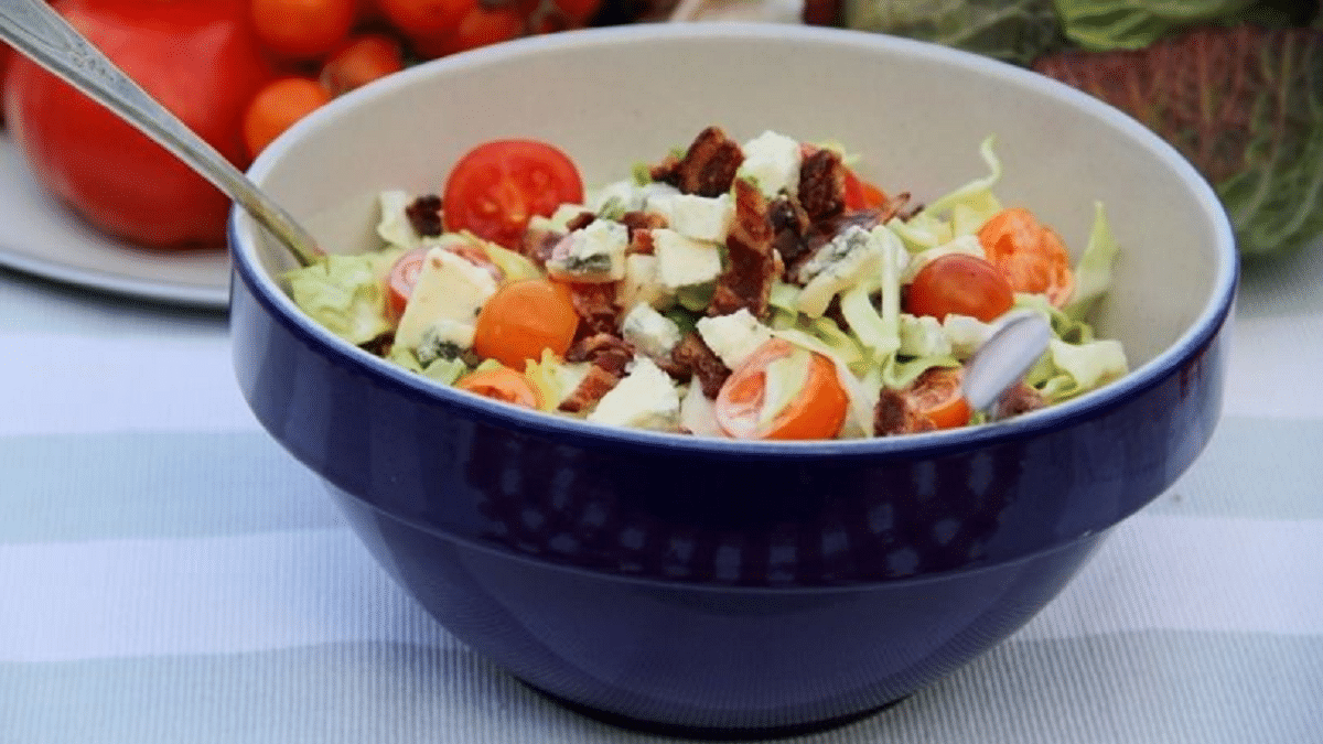 Blue bowl on striped cloth filled with salad
