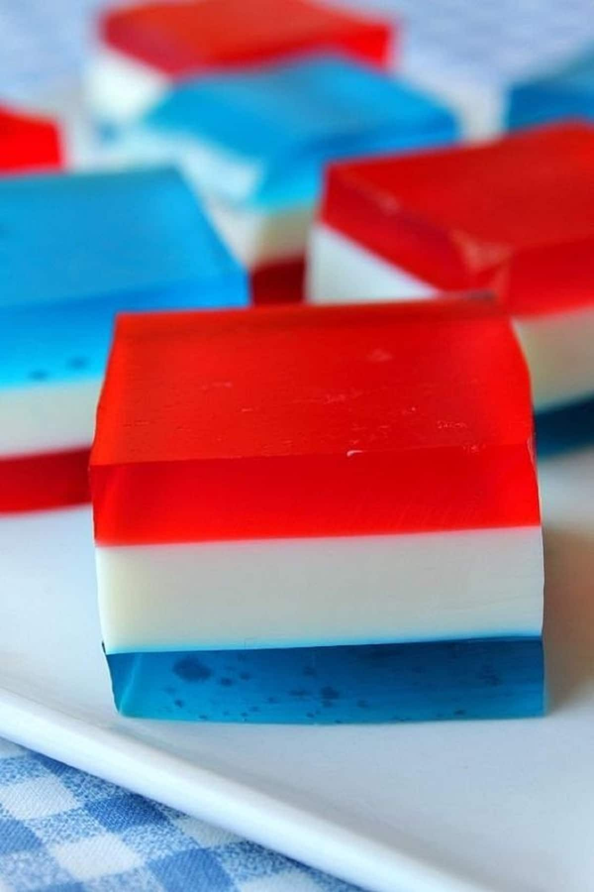 Layered red white and blue jello squares on white platter on blue checked napkin