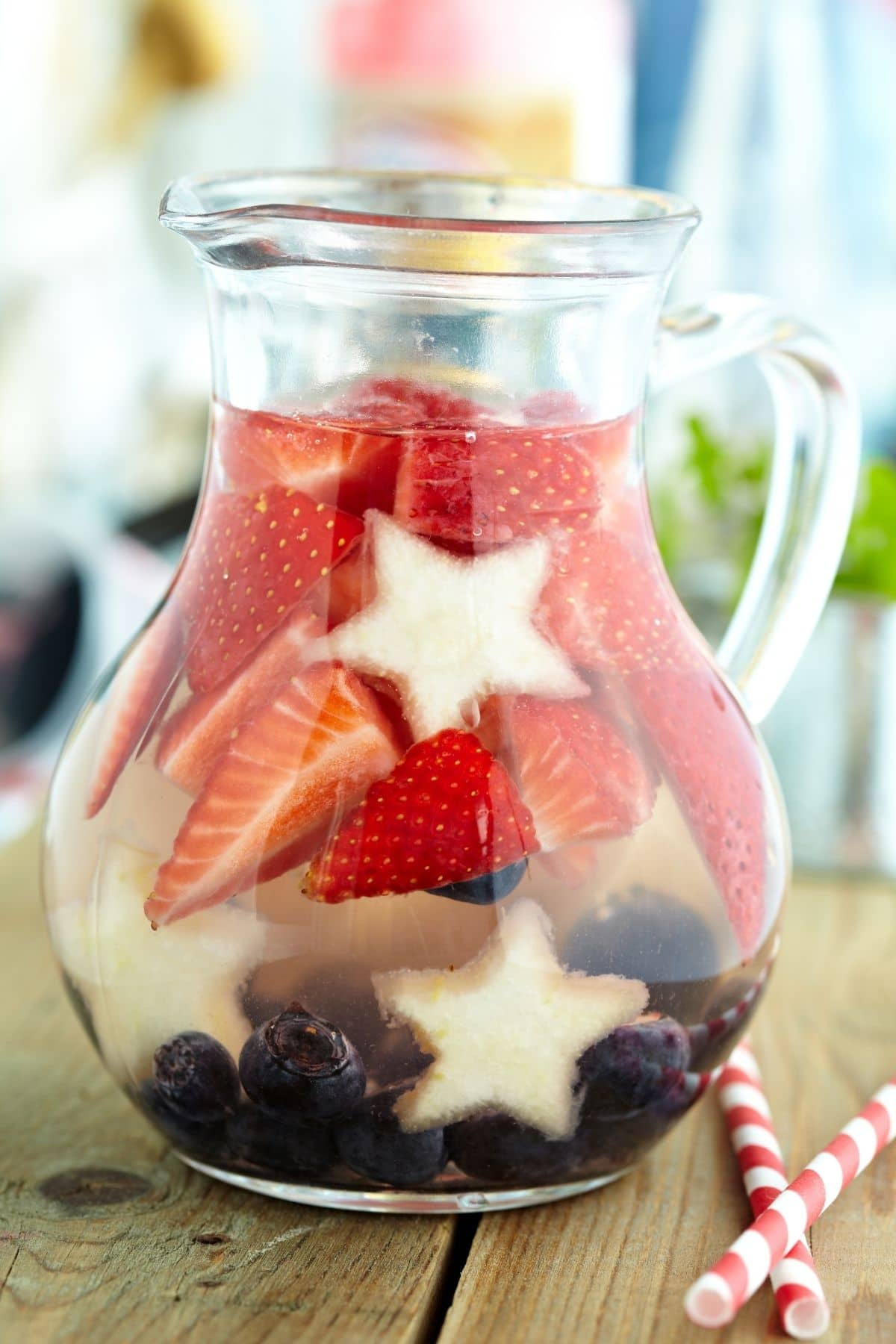 Glass pitcher filled with clear liquid strawberries blueberries and pineapple stars