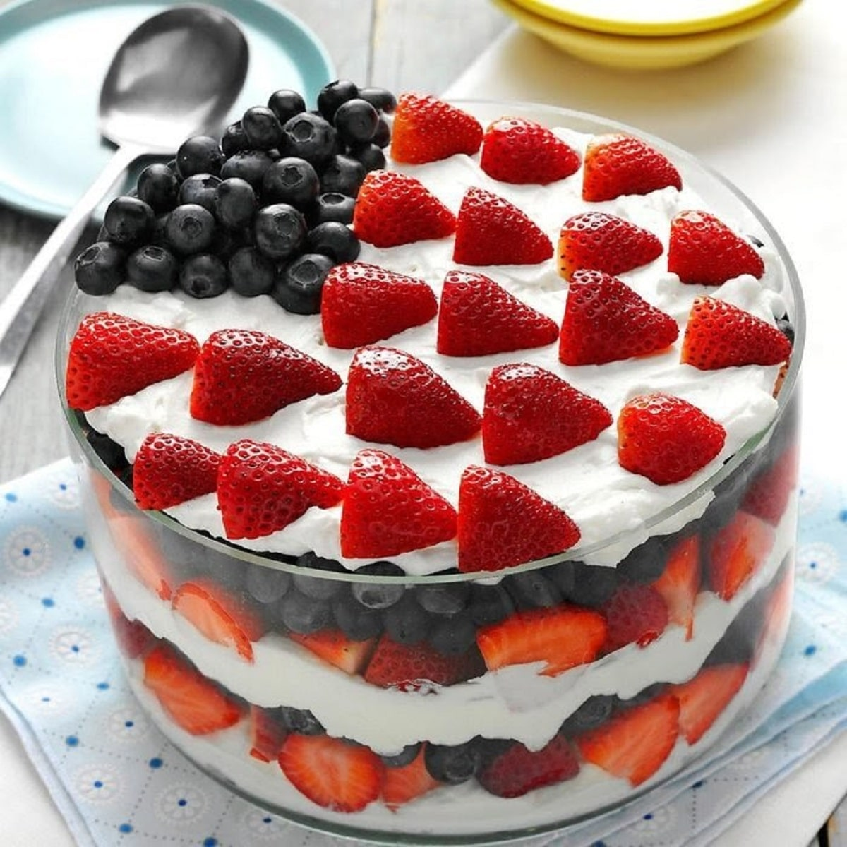 Large trifle bowl layered with cool whip strawberries and blueberries