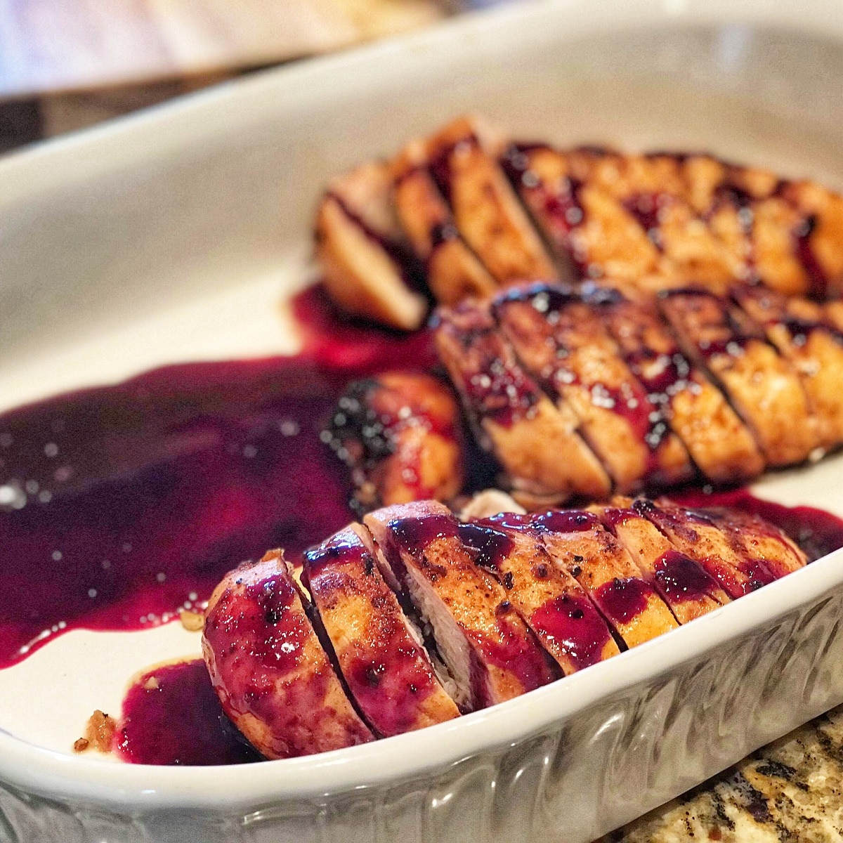 White baking dish with sliced chicken breasts in blueberry topping