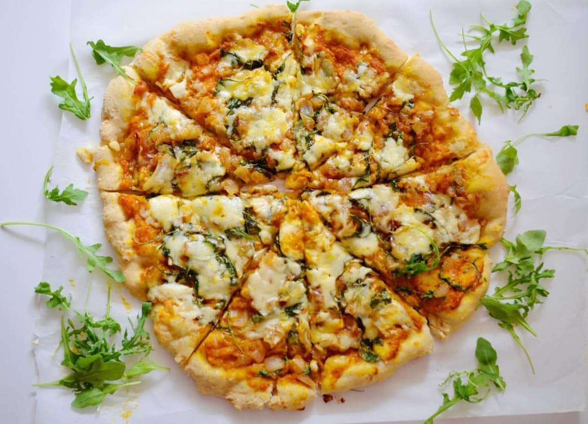 Savory Pumpkin Pizza topped with sweet onion, garlic, arugula, parmesan, havarti cheeses and pumpkin puree