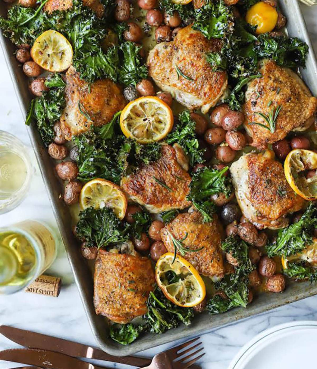 Sheet Pan Lemon Rosemary Chicken with kale, lemmon slices, rosemary and marble potatoes in a baking sheet