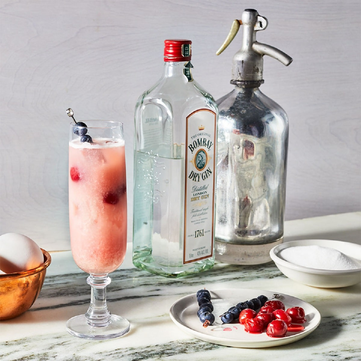 Tall glass with pink drink and blueberries next to bottles of gin and plate of berries