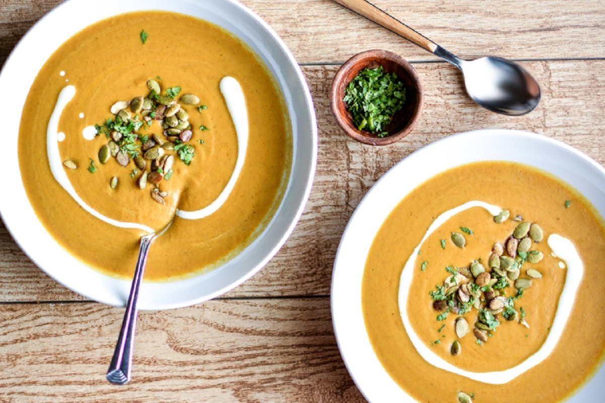 bowls of Spicy And Creamy Pumpkin Soup With Cashewson a wooden table