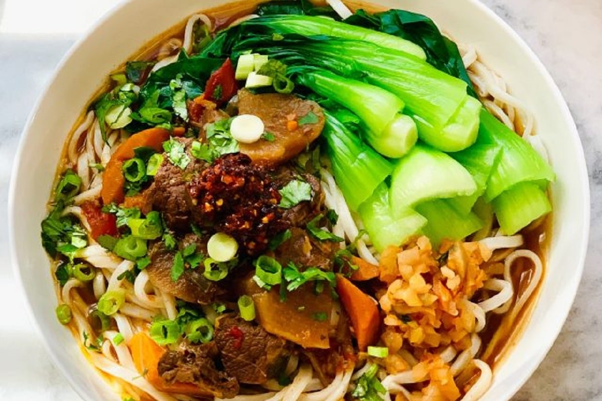 A bowl of Chinese Beef Noodle Soup with chili