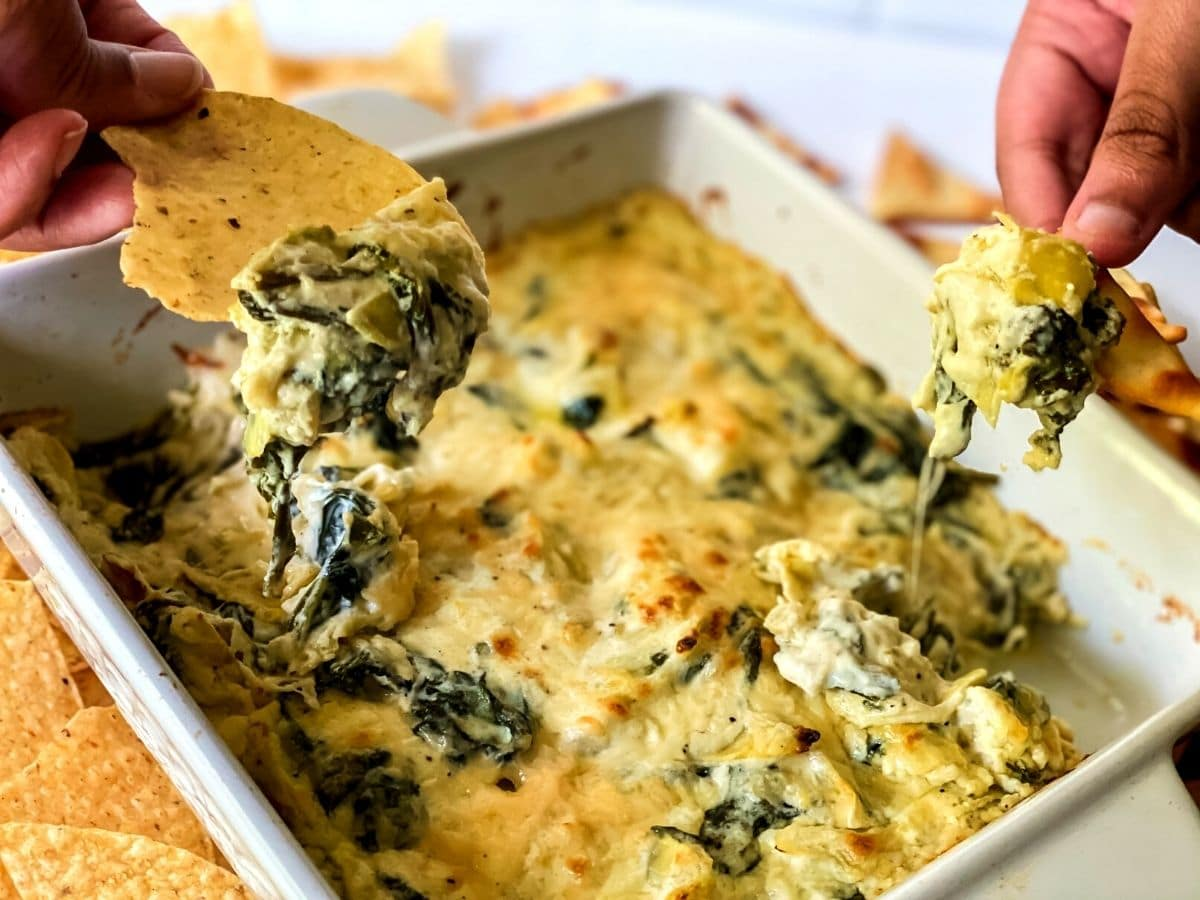 Two hands dipping chips into white bowl of spinach dip